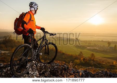 View of cyclist standing with mountain bike on hill trail at sunset. Man in the orange jacket, with helmet, black sunglasses and red backpack. Landscape with green field, hill and rocks. Spring season. Countryside.