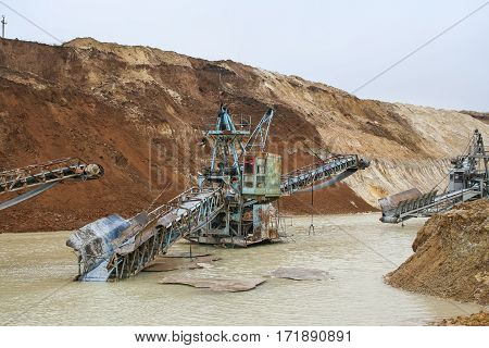 Clay quarry near the town of Pology in the Zaporizhya region of Ukraine flooded heavy rains. Equipment for mining of refractory clay - conveyor loader self-propelled crawler electric. March 2006