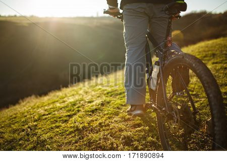 Closeup of cyclist man legs riding mountain bike on outdoor trail on the green field. Low angle. Detail of the bicycle. Wheel and bottle. Legs and shoes. Spring season. Travel in the countryside.