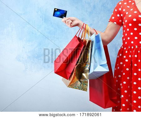 Woman holding shopping bags and credit card on color background