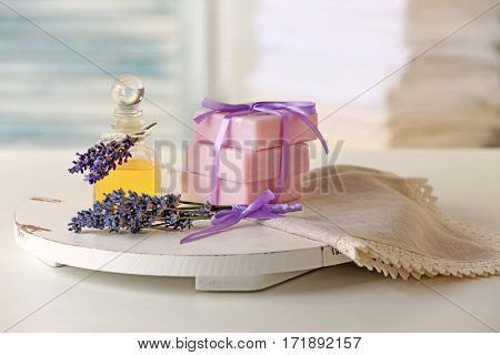 Glass bottle of essential oil and tied stack of soap with lavender on table