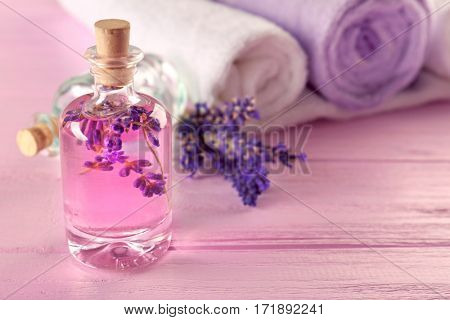 Bottle with lavender aroma oil and towels on pink wooden background