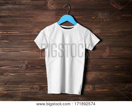Blank white t-shirt against wooden background