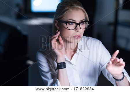 IT girl working . Pleasant delighted concentrated woman sitting in the office and using modern technologies while expressing interest