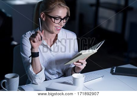 Pleasant working hours. Smiling cheerful attractive secretary sitting in the office and making notes while expressing positivity