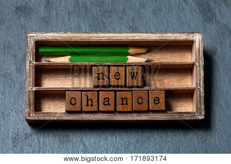 New chance phrase. Motivation and positive expectations concept. Vintage box, wooden cubes with old style letters, green pencils. Gray stone textured background. Close-up, up view, soft focus.
