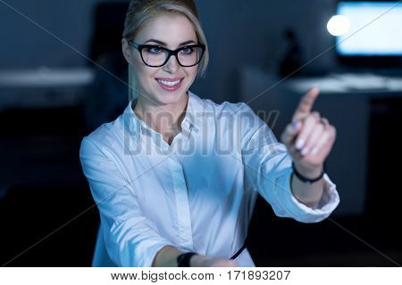 Developing new programming language. Smiling young professional IT woman sitting in the office and using modern technologies while working on the project