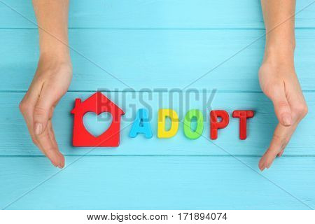 Female hands, word ADOPT and figure in shape of house on wooden background