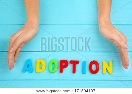 Female hands and word ADOPTION on wooden background