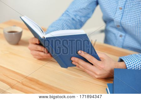 Young man reading book while sitting at table, closeup