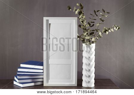 Pile of books, frame and vase with plant on table against grey background