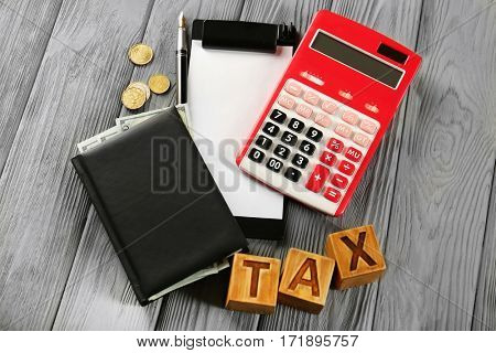 Wooden cubes with word TAX and calculator on table