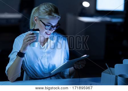 Testing new gadgets. Cute young smiling IT woman sitting in the office and using tablet while working on the project