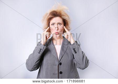 Portrait of astonished senior woman with eyeglasses on grey background