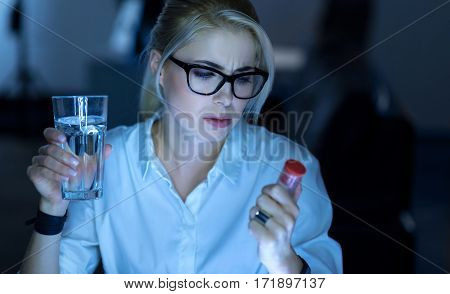 Suffering from the pain. Serious exhausted tired businesswoman sitting in the office and holding pills while suffering from pain