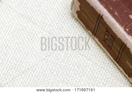 Well loved and read leather bible on simple burlap background space for text