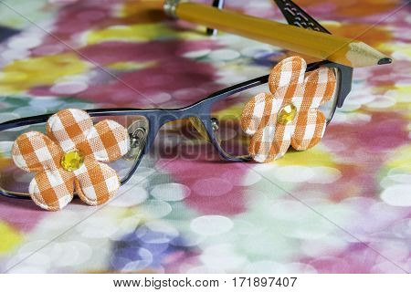 Closeup of girl glasses with bright flowers on eyes lenses and pencil resting on top joyful nerd concept
