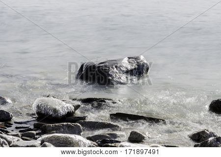 Ice capped rocks on winter shoreline with flowing waters high contrast scene