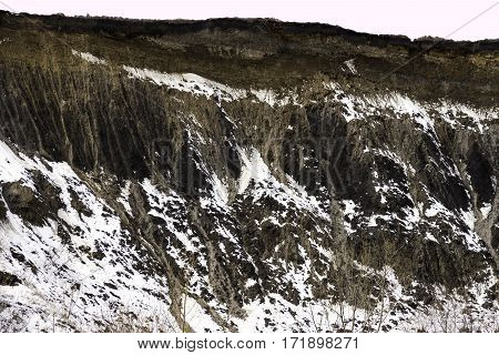 Sheer cliff with trails of soil erosion in stripes down fromn the top environment concept