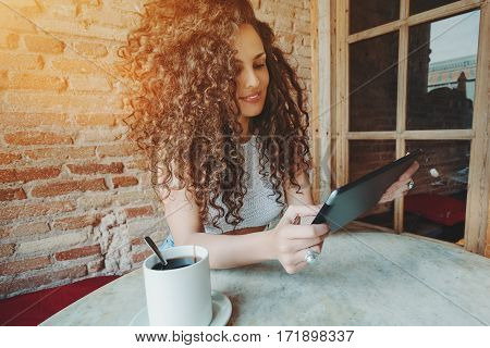 Happy young curly brunette woman using digital tablet and drinking tea while sitting in coffee shop attractive female freelancer holding touch pad smiling for the camera while resting in cozy cafe