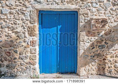 Blue door  with stone wall in Santorini, Greece.
