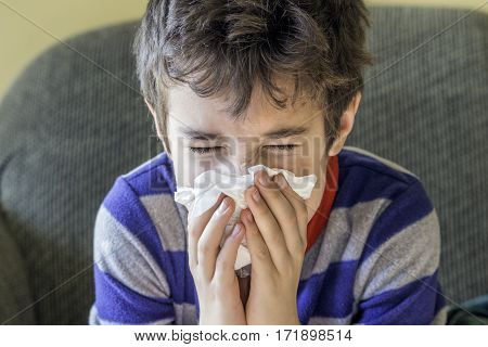 Young boy sneezing into a tissue while at home sick in pyjamas cold and flu healthcare concept