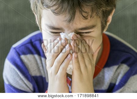 Closeup of sick boy in pyjamas sneezing into a tissue health cold and flu concept