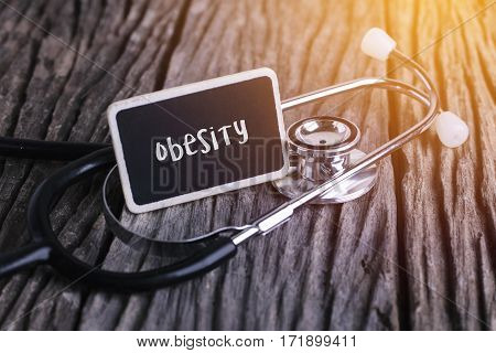 Stethoscope On Wood With Obesity Word As Medical Concept.