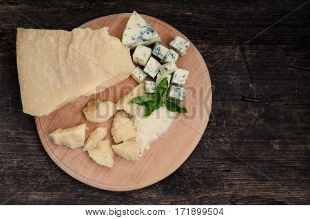 Grated Parmesan and sliced Blue cheese with basil on wooden chopping board on old wooden background. Tasty appetizers. Top view. Copy space.