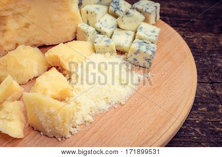 Grated Parmesan and sliced Blue cheese with basil on wooden chopping board on old wooden background. Tasty appetizers. Selective focus.
