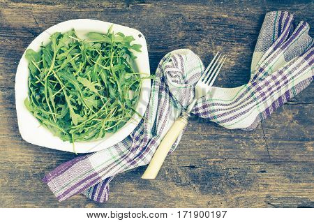 Fresh arugula in a plate with a fork on rustic wooden background with place for text. Healthy organic diet vegan food concept. Green meal. Top view. Copy space.