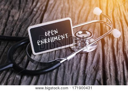 Stethoscope On Wood With Open Enrollment Word As Medical Concept.