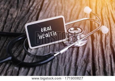 Stethoscope On Wood With Oral Health Word As Medical Concept.