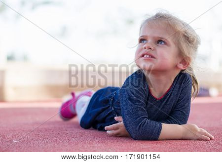 Cute little child blonde toddler girl playing outdoors lying at playground.