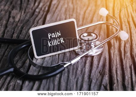 Stethoscope On Wood With Pain Killer Word As Medical Concept.