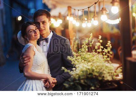 wedding couple at night lightin. Cafe along with decoration lights