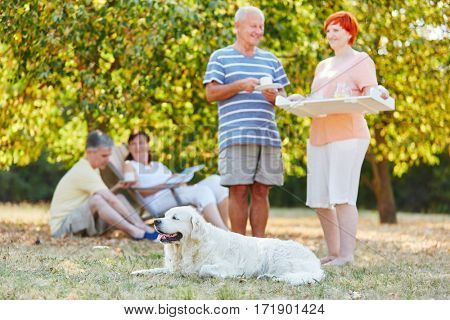 Group of seniors with dog in the park drinking coffee on their summer holidays