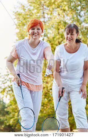 Two women playing badminton in the nature having fun