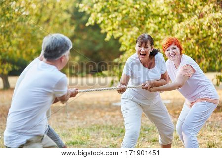 Group of senior friends playing tug of war in summer in the park