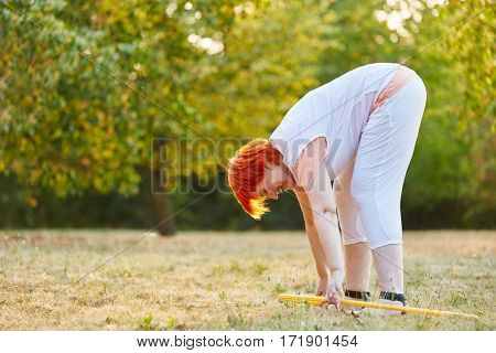 Active senior woman doing gymnastics with a hoop in summer