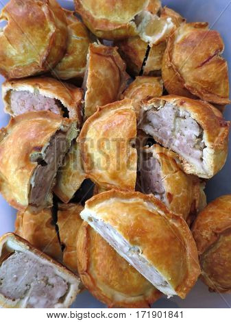 A pile of individual English pork pies cut in halves with golden pastry