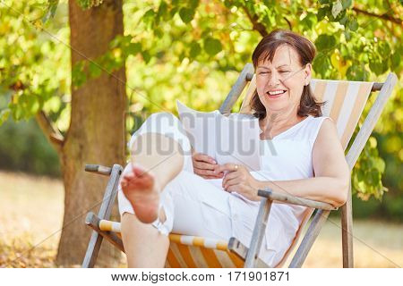 Relaxed senior woman reading on a deck chair in summer in the gardent