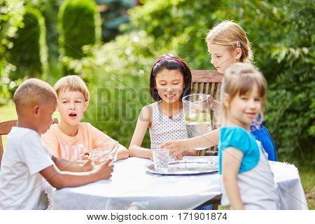 Childrens birthday party with kids drinking water in summer