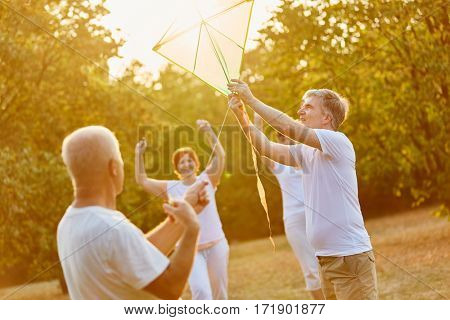 Group of seniors kite flying as a team in autumn in the park