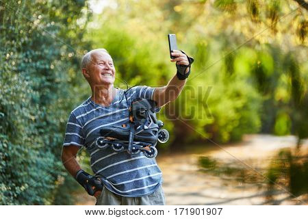 Active senior man taking a selfie with his inline skates