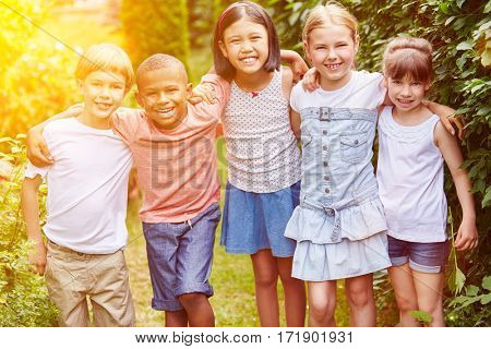 Group of children smiling as friends together in summer in garden