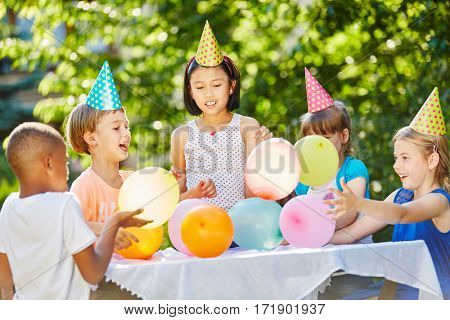 Many kids celebrate birthday together with balloons and party hats