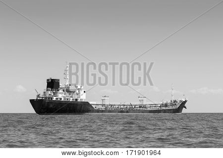 Black and White Oil transport ship over seacoast skyline
