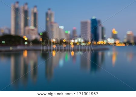 Twilight blurred bokeh office building with reflection in public park abstract background