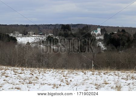 A graveyard and church on a snow covered landscape.
